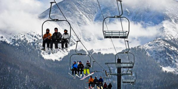 mountain skiers riding on chair lift