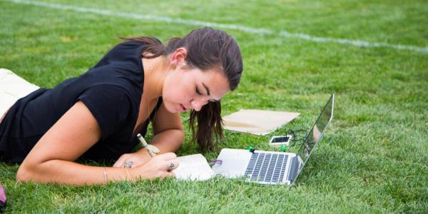 student taking notes, lying on grass