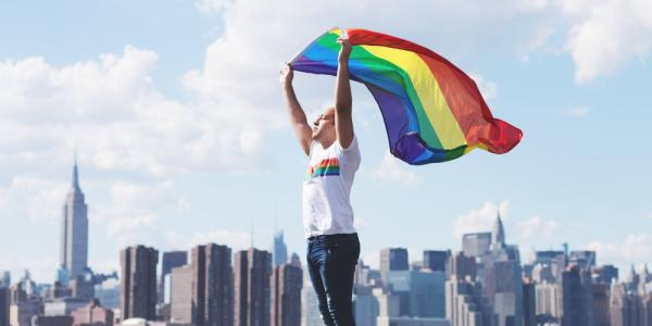 Eliel Cruz waves gay pride flag with NYC skyline behind