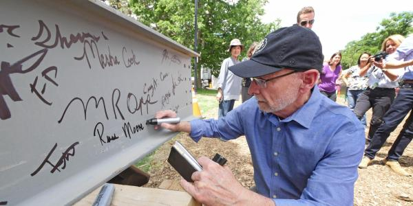 Provost Russ Moore signing Ramaley beam