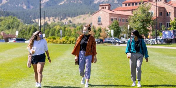 friends in masks walking on campus