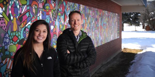 Student with mentor, posing in front of colorful mural