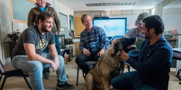 Engineering students and professor gathered around a big, fluffy dog in their laboratory