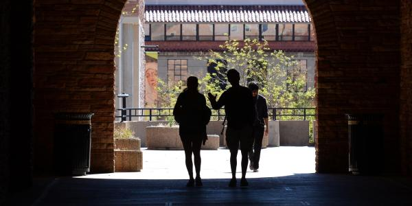 People walk through a tunnel on the CU Boulder campus