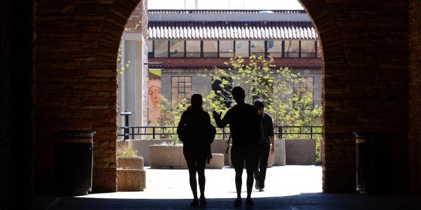 Silhouette of students walking under archway on campus