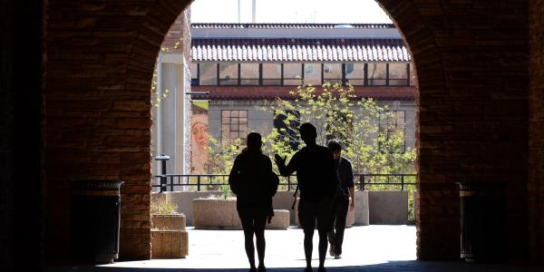 Silhouettes of students walking under archway on campus