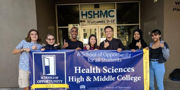 Students hold Health Sciences High & Middle College Schools of Opportunity banner