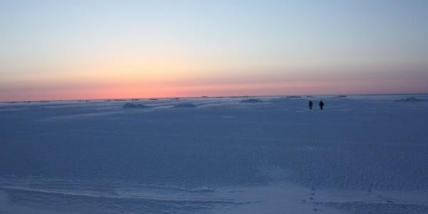 Researchers walking on sea ice at sunset