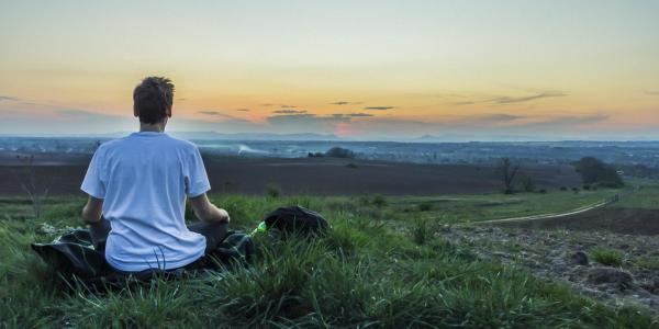 Man sits on hill looking out at city, mountains
