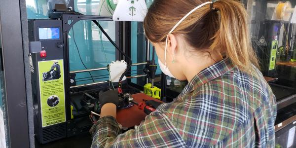 Rachel Sharpe conducts repairs on a 3D printer.