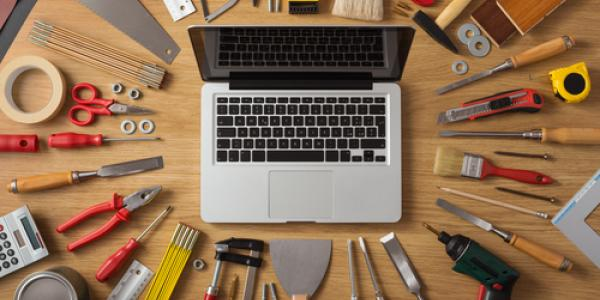 Stock image of a laptop computer surrounded by tools