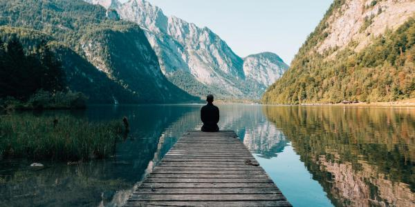 Person meditating by a lake