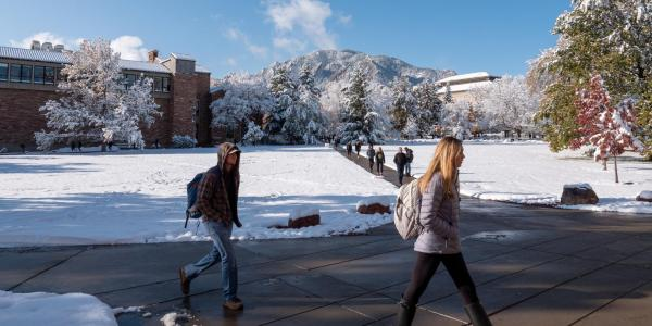 students walking across a snowy campus