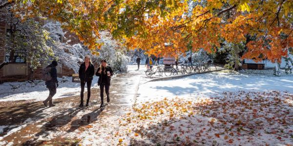 Students walking across a snowy campus, with colorful fall trees