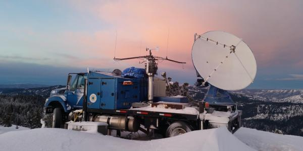 A radar dish mounted on the bed of a truck.