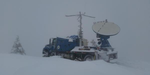 A radar dish mounted on the bed of a truck in the snow.