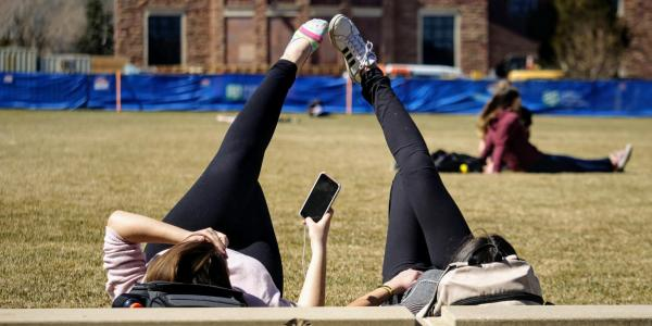Two students lying in the grass of Farrand Field on the first day of spring