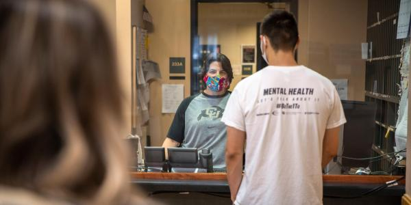 Staff member wearing a mask helps a student on campus