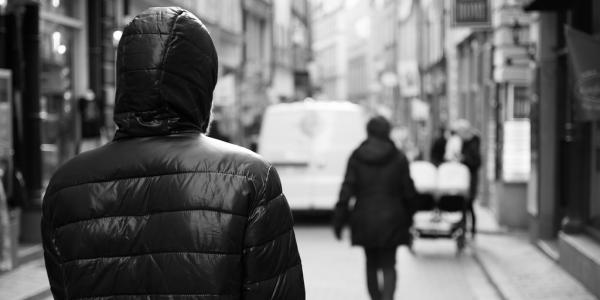 Person in hoody stalking woman on empty street