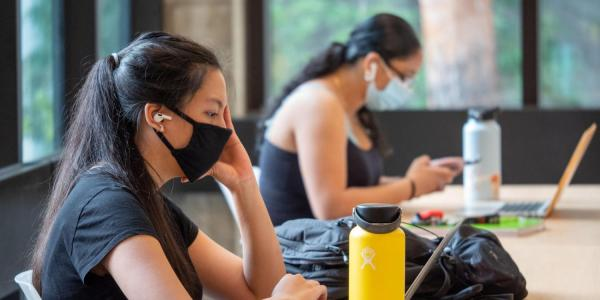 students working on laptops while wearing masks