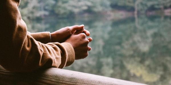 Person holds hands together, looking outside