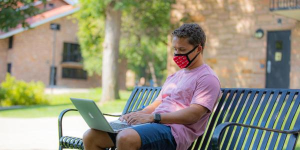 student working on laptop on campus