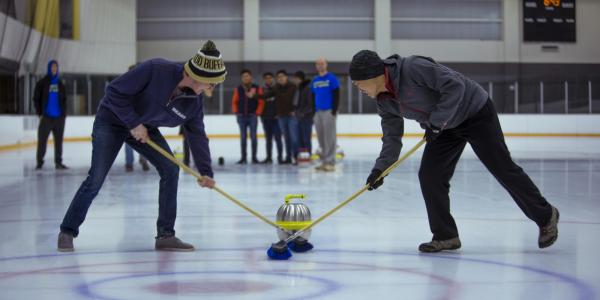 Students curling on the ice rink at The Rec