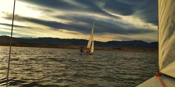CU Boulder student sails at sunset on Colorado lake