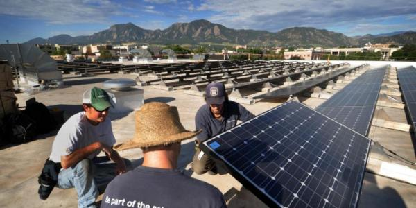 Workers install solar panels on CU Boulder rooftop