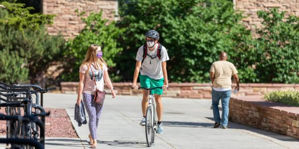 Student riding a bike on campus, while a friend walks alongside him