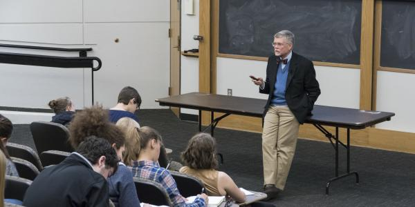 A professor stands in front of a class, taking notes in an auditorium