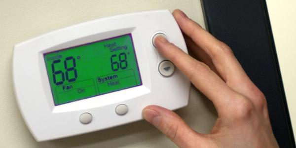 Person adjusts temperature on thermostat