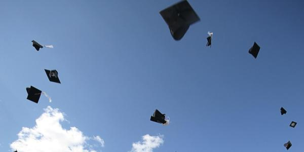A number of graduation caps are suspended in air with a blue-sky backdrop.