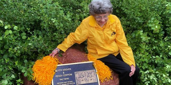 Peggy Coppom sits next to a plaque honoring her and her late twin sister, Betty Hoover. (Photo by Sarah Adderholt/University of Colorado)