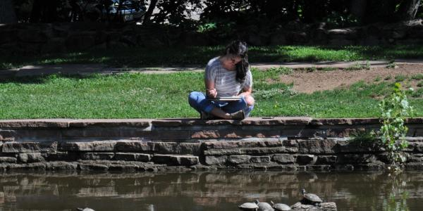 Student studying by Varsity Lake.