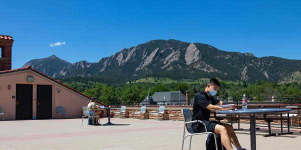 Student sitting on the CASE Building deck overlooking the Flatirons.