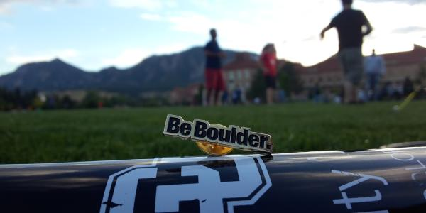 A Be Boulder pin sits atop poster paper on a field on campus with people in the background.