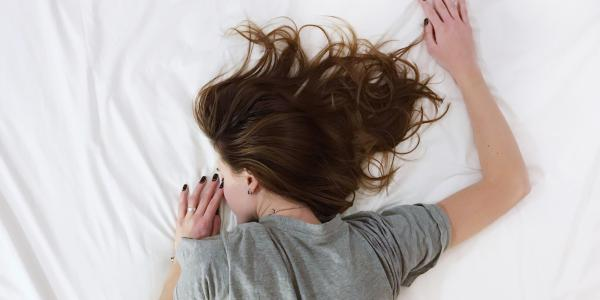 A stock photo of a woman sleeping on a bed