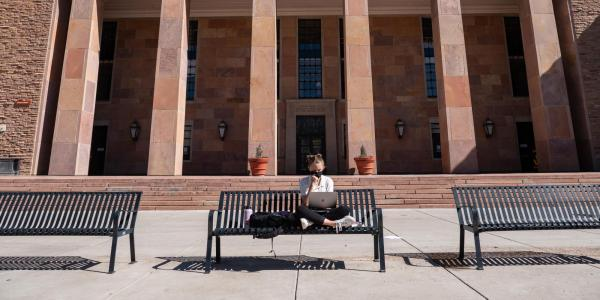 student sitting on a bench at Norlin Quad