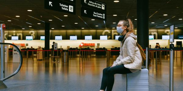 Woman sits in an airport while wearing a mask.