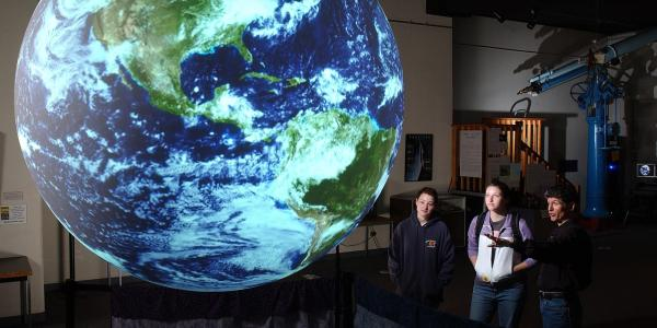 People look at an image of Earth projected on a sphere.