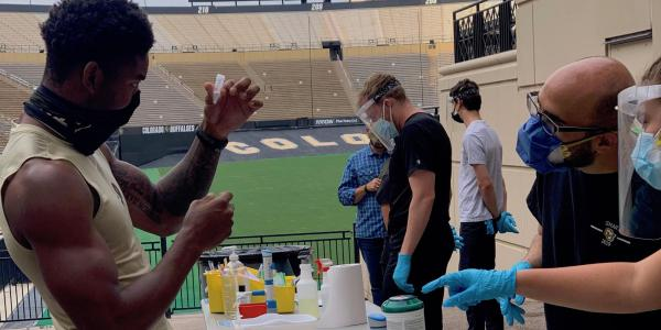 CU Boulder athlete holds up a vial for testing his saliva for the coronavirus.