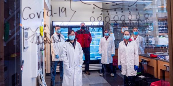 """Lab members stand behind glass with the words """"COVID Warriors"""" written on it in marker"""