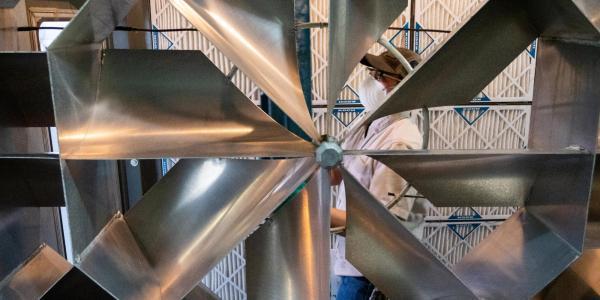 Maintenance worker viewed through a ventilation fan.
