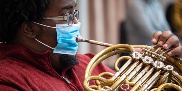 Playing French horn with a mask