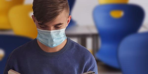 Student reads in classroom while wearing a mask.