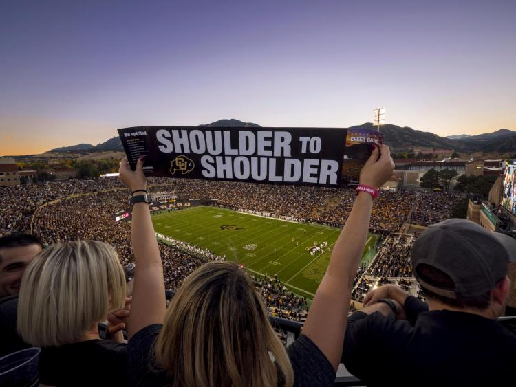 "A ""shoulder to shoulder"" sign at a homecoming football game."