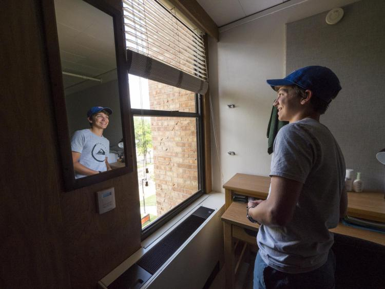 Student looks out window during move-in
