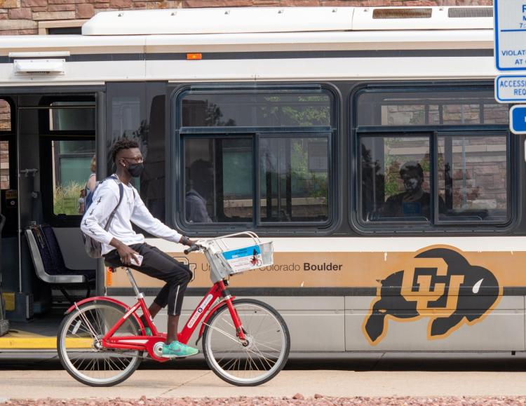 Student riding a bike past a Buff Bus on campus