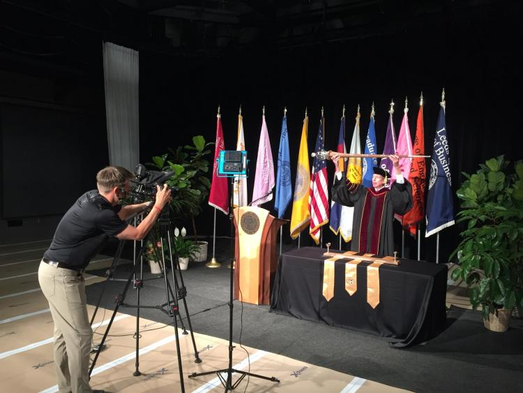 A camera records Bud Coleman as he lowers the ceremonial mace